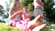 Children Sitting Outdoors On Grass And Clapping video