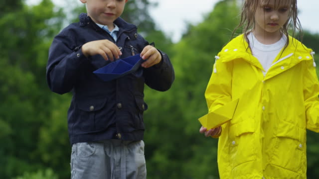 Children with Paper Boats Standing in Puddle video