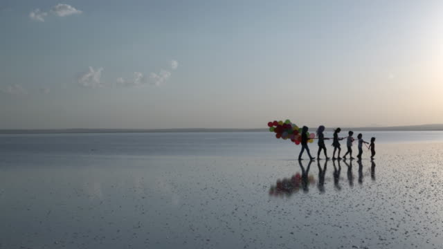 Childrens are walking on the water with color ballons video