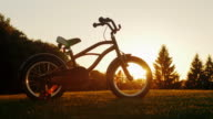 Children's bicycle standing on a green lawn on the background of the setting sun. Concept - children's dreams, a happy childhood video