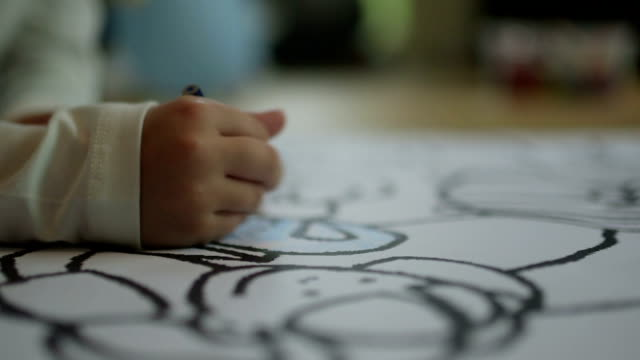 CLOSE UP SELECTIVE FOCUS Child's hand coloring din coloring book video