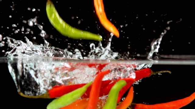 Chili peppers falling in water video