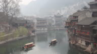 chinese boats rowwing, huts with red lanterns on the shore video