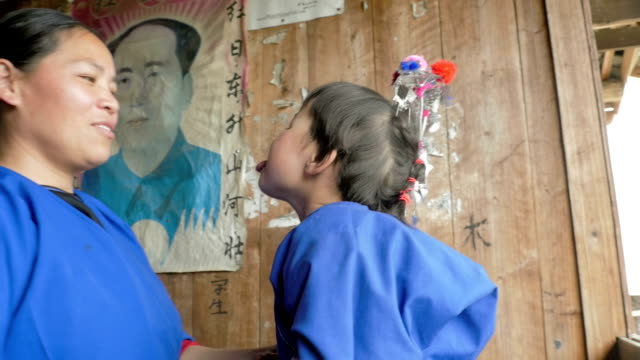 Chinese child and mother infront of a Mao poster video