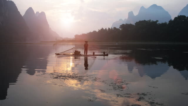 Chinese Fisherman throwing fishing net at sunrise video