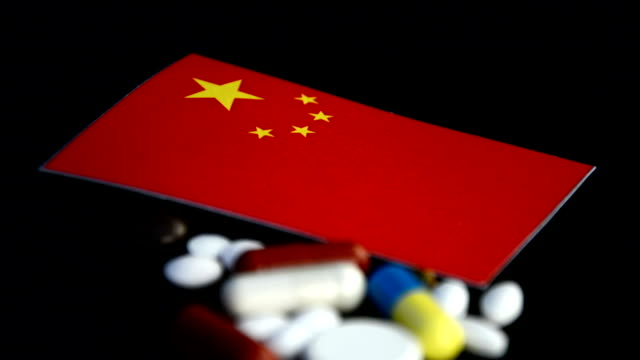 Chinese flag with lot of medical pills isolated on black background video
