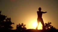 Chinese gymnastics Tai Chi. Man does exercises in the rays of the rising sun video