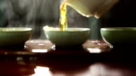 Chinese tea is poured into three porcelain cups. video