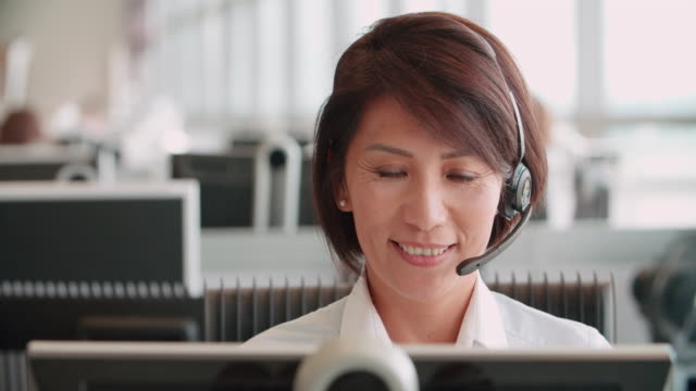 Chinese woman working in a call centre using a headset video
