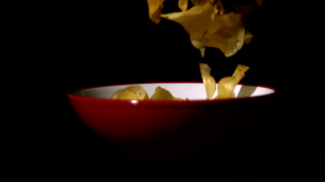 Chips falling into bowl on black surface video