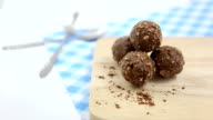 Chocolate balls on wooden with sprinkle chocolate powder video