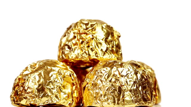 Chocolate bonbons wrapped in gold foil rotating on a white background video