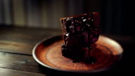 Chocolate dripping on brownie cake. Dark chocolate flowing on chocolate cake video