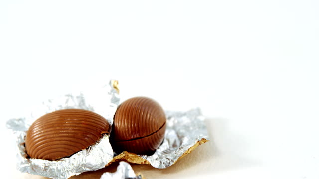 Chocolate Easter eggs in foil on white background video
