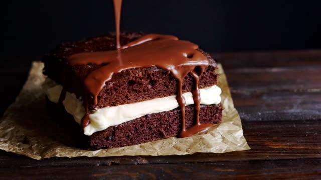Chocolate icing on cake. Chocolate glaze pouring on homemade dessert video