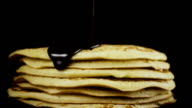 Chocolate is poured onto a pancake against a black background. Slow motion video