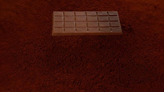Chocolate Tablet falling on Black Chocolate Powder, Slow motion 4K video