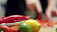 Chopping a red pepper. Shallow focus. Lemon and lime in focus. video