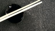 Chopsticks and soy sauce on black stone slate video