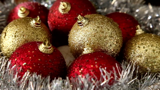 Christass decorations red and golden balls on rotating table close-up. video
