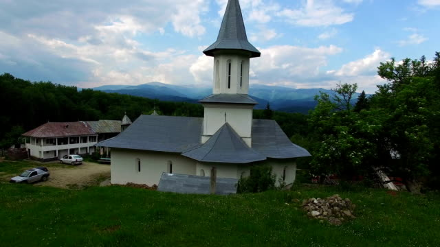 Christian church on top of green hill, aerial view, camera rising video