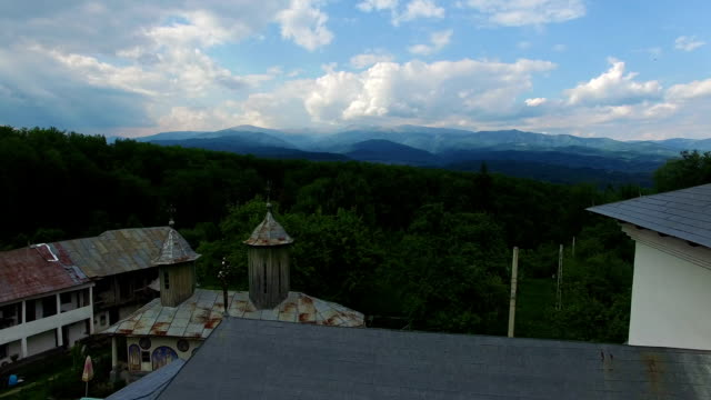 Christian church on top of green hill with mountain range, cam fly video