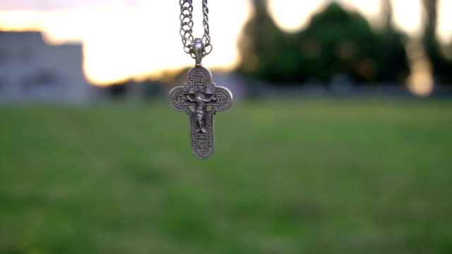 Christian cross on a chain on the background of sunrise video