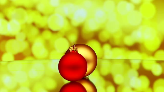 christmas baubles rotating on reflective surface video