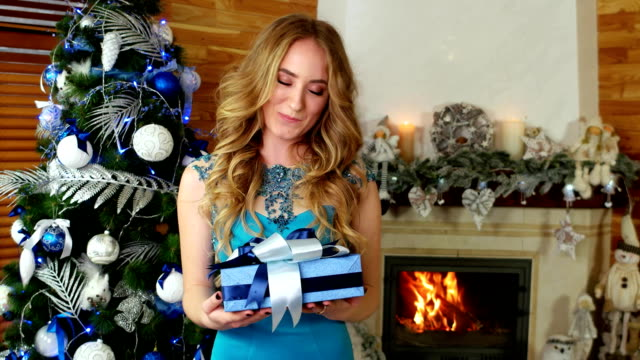 Christmas gift, portrait of female with Christmas gift in hand, girl gives a festive wrapped present, on Christmas Eve, New Year's Eve video