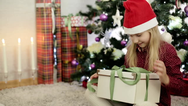 Christmas gift surprise. Blond girl presented with a gift box. video