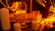 Christmas lights, white candles, pine cones in a vase decorate the room. video