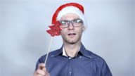 Christmas man in elegant shirt and santa claus hat smiling over grey background. video