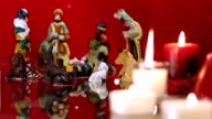 Christmas nativity scene with candles on red video