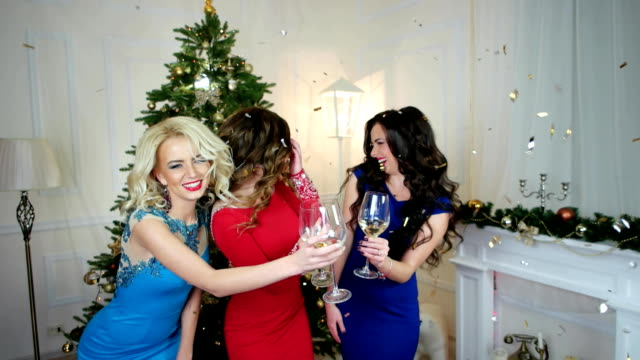Christmas party, girls drinking wine, dancing having fun, group of people celebrating the New Year, laughing at the background of the Christmas tree, golden confetti video
