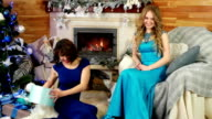 Christmas presents, joyful beautiful female give a gift, friends exchange surprises, New Year's Eve, girls sit by the fireplace under the Christmas tree, winter holidays video