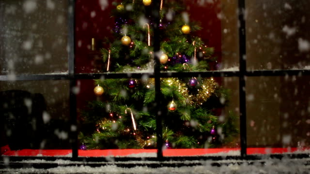 Christmas Tree at window with snow falling - DOLLY video
