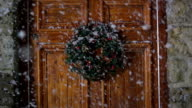 Christmas Wreath on door, Snowing - DOLLY video