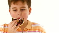 Chubby boy eating chocolate donut on white background. video