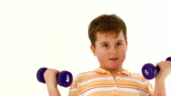 Chubby boy lifts dumbbells on white background. video