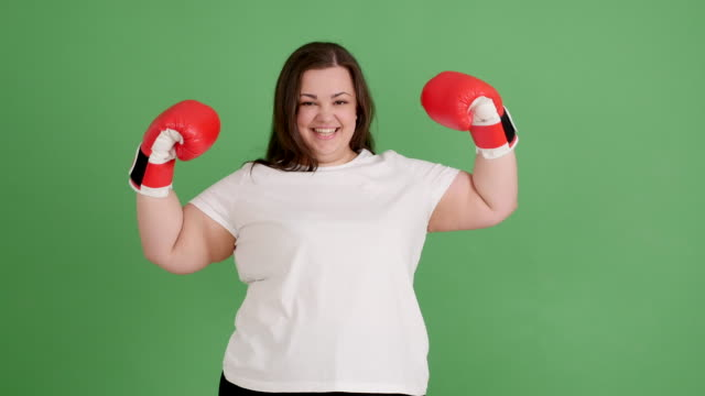 chubby girl with boxing gloves on a green screen video