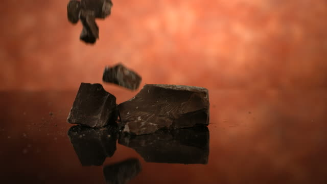 Chunks of chocolate falling, slow motion video