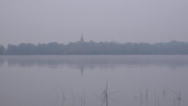 Church tower on lake shore in dense fog in autumn morning. Zoom out. FullHD video