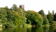 Church tower rising above tall trees at Lymm dam Cheshire video