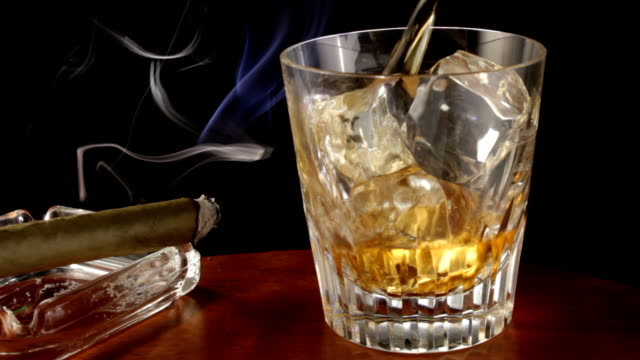 Cigar and glass of whisket on bar video