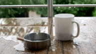 Cigarette in ashtray and cup of coffee on a table in rain water video