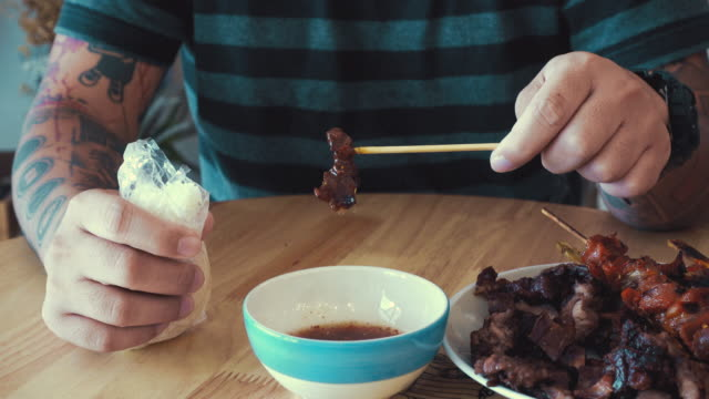 Cinemagraphs : Young man dipping barbecue sauce. video