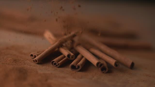 Cinnamon falling onto cinnamon sticks video