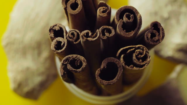 Cinnamon sticks slowly rotating a yellow background video