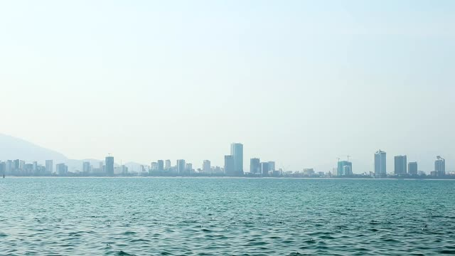 City on horizon in fog above blue sea water. video