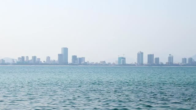 City on horizon in fog blue sea water panning slow motion. video